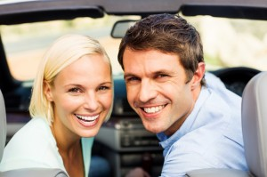 Cheerful Couple In Convertible Car Enjoying Road Trip